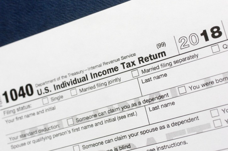 FILE - This July 24, 2018, file photo shows a portion of the 1040 U.S. Individual Income Tax Return form for 2018 in New York. The Child Tax Credit changed considerably in 2018. The standard deduction nearly doubled for 2018, leaving many taxpayers wondering whether it's financially worth it to itemize on their tax returns anymore. (AP Photo/Mark Lennihan, File)