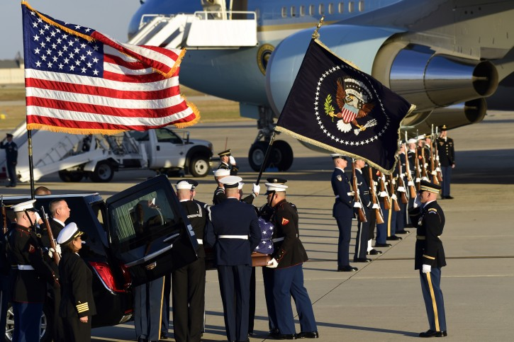 The flag-draped casket of former President George H.W. Bush is carried by a joint services military honor guard to a hearse at Andrews Air Force Base in Md., Monday, Dec. 3, 2018. (AP Photo/Susan Walsh)