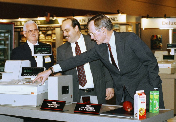 FILE - In this Feb. 4, 1992 file photo, President George H. W. Bush, right, pushes the keys on a new high technology cash register under the watchful eyes of Leo Hardy, left, and Bob Graham, center, during a visit to the National Grocers Association trade show in Orlando, Fla. (AP Photo/Barry Thumma)