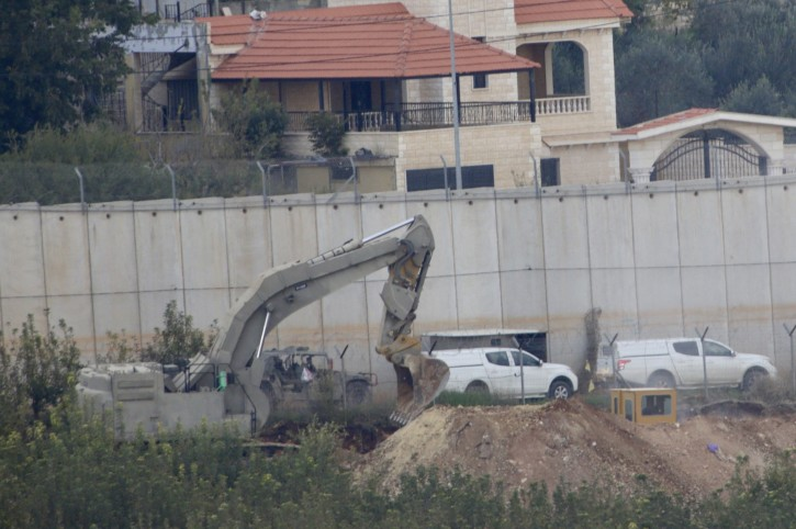 """Israeli military digger works on the border with Lebanon in the northern Israeli town of Metula, Tuesday, Dec. 4, 2018. The Israeli military launched an operation on Tuesday to """"expose and thwart"""" tunnels built by the Hezbollah militant group it says stretch from Lebanon into northern Israel. (AP Photo/Ariel Schalit)"""