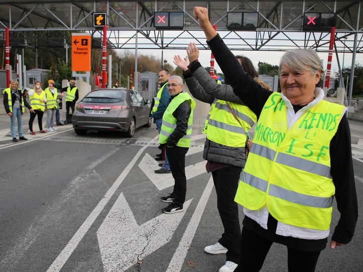 """A demonstrator wearing a yellow jacket reading """" Macron give us the wealth tax"""" protests at the toll gates on a motorway at Biarritz southwestern France, Wednesday, Dec.5, 2018.The concessions made by French president Emmanuel Macron's government in a bid to stop the huge and violent anti-government demonstrations seemed on Wednesday to have failed to convince protesters, with trade unions and disgruntled farmers now threatening to join the fray.(AP Photo/Bob Edme)"""
