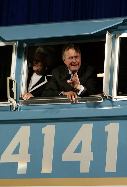 FILE - In this Oct. 18, 2005, file photo, former President George Bush and his wife Barbara wave out the window of a new locomotive numbered 4141 in honor of the 41st president at Texas A&M in College Station, Texas.  (AP Photo/Pat Sullivan, File)