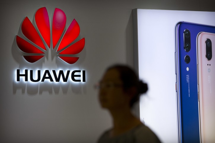 FILE - In this July 4, 2018, file photo, a shopper walks past a Huawei store at a shopping mall in Beijing. Canadian authorities said Wednesday, Dec. 5, 2018,  that they have arrested the chief financial officer of China's Huawei Technologies for possible extradition to the United States. (AP Photo/Mark Schiefelbein, File)