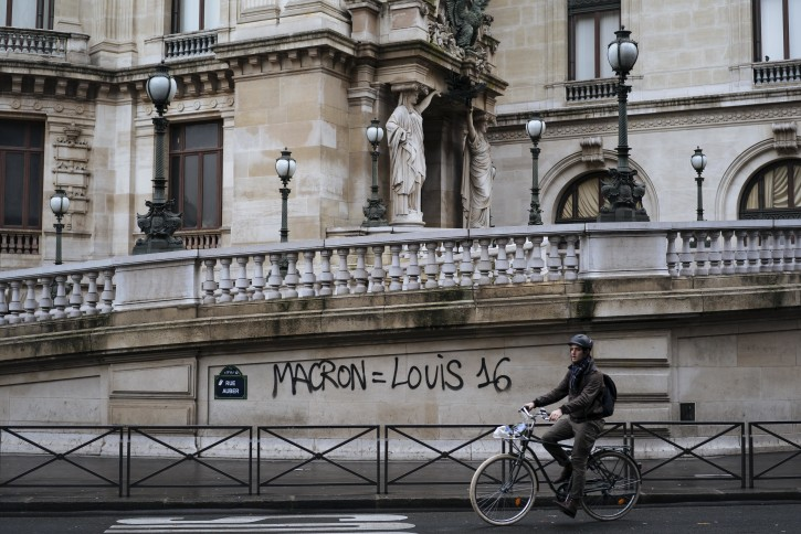 """FILE - In this Dec. 2, 20118 file photo, a man rides his bicycle past by a graffiti on the Paris Garnier Opera house in Paris that reads: """"Macron is equal to Louis 16"""", referring to the King of France during the French Revolution in 1789.  (AP Photo/Kamil Zihnioglu, File)"""