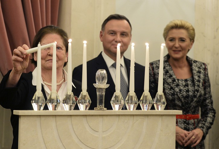 A members of the Jewish community lights a  candle as Polish President Andrzej Duda, center, and wife Agata Kornhauser-Duda watch the ceremony celebrating Hanukkah, the Jewish festival of lights, at the presidential palace in Warsaw, Poland, Sunday, Dec. 9, 2018. (AP Photo/Alik Keplicz)