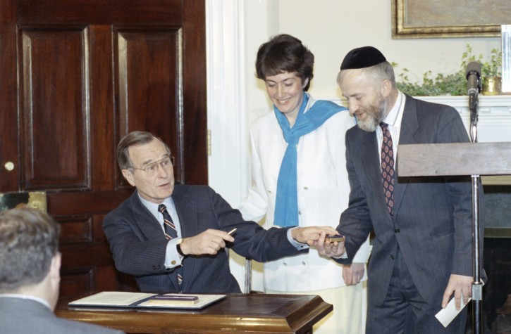 President George H.W. Bush  hands a pen to Vladimir Raiz after signing a Passover message at the White House, Washington on Wednesday, April 4, 1990 as his wife Karmella looks on.  Both recently emigrated from the Soviet Union to Israel. (AP Photo/Barry Thumma)