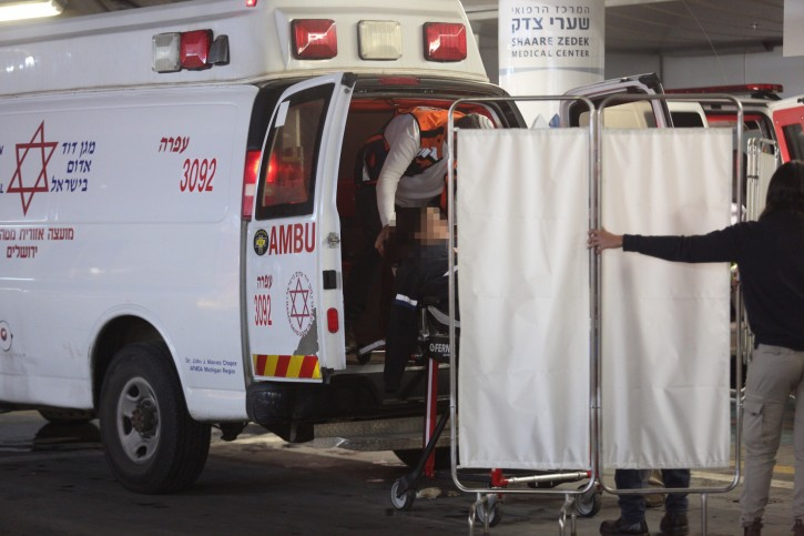 Israeli security and medical personnel evacuate an Israeli woman from the ambulance at the Shaarei Tzedek Hospital in Jerusalem, after she was was seriously injured in a terror attack in Ofra, December 9, 2018. Photo by Hadas Parush/Flash90