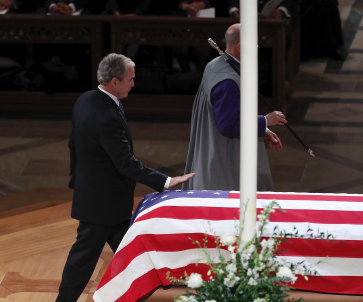 Former United States President George W. Bush touches the casket of his father, former United States President George H. W. Bush, during the funeral services at the National Cathedral in Washington, DC, USA, 05 December 2018. EPA