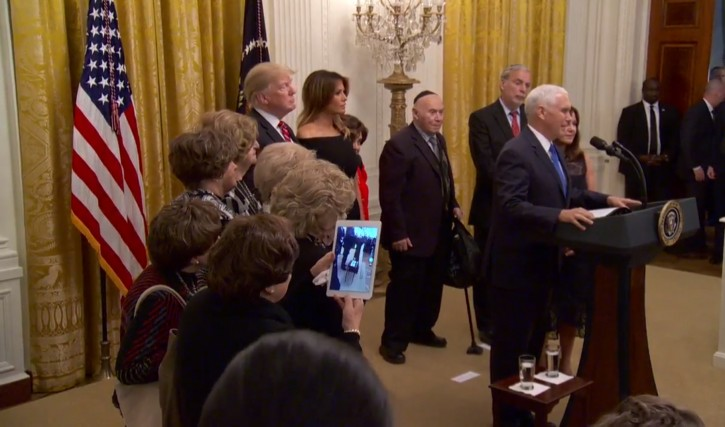 A holocaust survivor uses her iPad to capture VP Mike Pence speak at the annual Hanukkah reception at the White House. A group of Holocaust survivors were part of a delegation to the event.