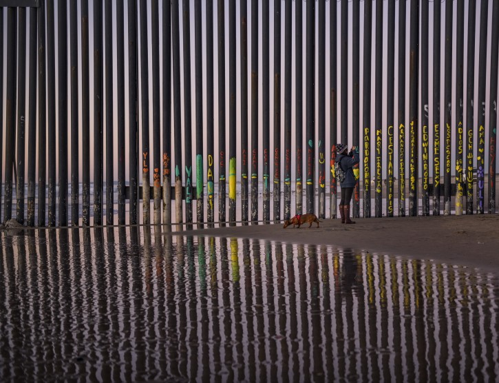 A woman takes a snapshot by the border fence between San Diego, Calif., and Tijuana, as seen from Mexico, Thursday, Jan. 3, 2019. Discouraged by the long wait to apply for asylum through official ports of entry, many migrants from recent caravans are choosing to cross the U.S. border wall and hand themselves in to border patrol agents. (AP Photo/Daniel Ochoa de Olza)