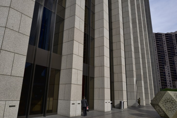 In this Jan. 8, 2019 photo people are towered by the front facade of the Bank of America Plaza Building in downtown Los Angeles. Companies are lining up to tell investors how much they made during the last three months of 2018, and the reports get going in earnest this upcoming week with Citigroup and a slew of other banks on deck.  (AP Photo/Richard Vogel)