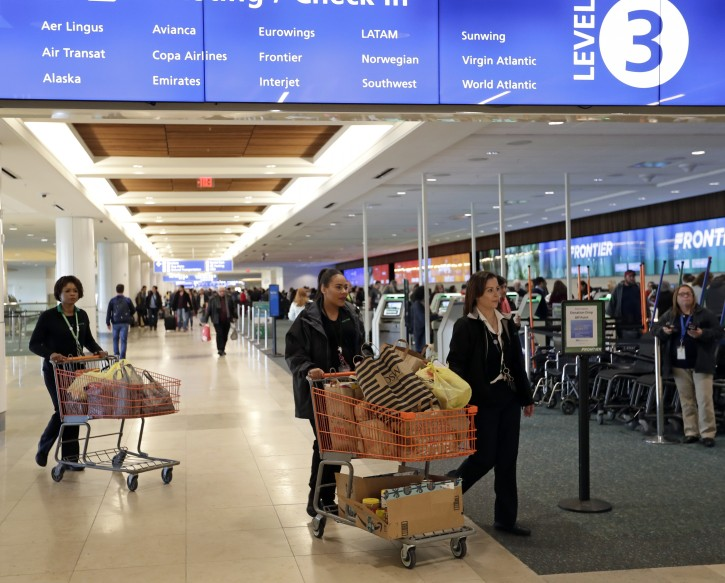 Frontier Airline employees move food and supplies in carts for TSA workers to a distribution center at Orlando International Airport Wednesday, Jan. 16, 2019, in Orlando, Fla. (AP Photo/John Raoux)
