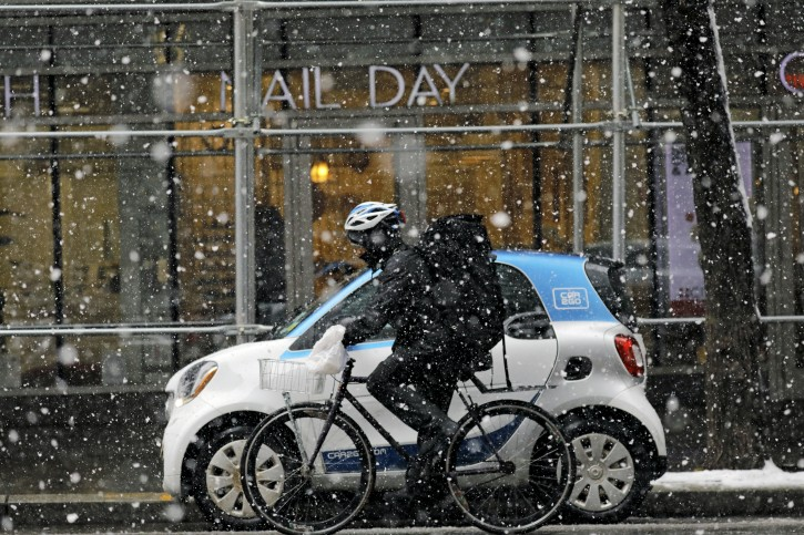 FILE - A man rides a bicycle in the snow during a late season snowstorm in New York, New York, USA, 21 March 2018. EPA