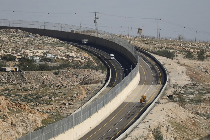 A view of cars driving on the Israeli side (R) and Palestinians side (L) of the road that separates between Israelis and Palestinians near the Issawiya neighborhood and Shuafat refugee camp in East Jerusalem, 10 January 2019. EPA