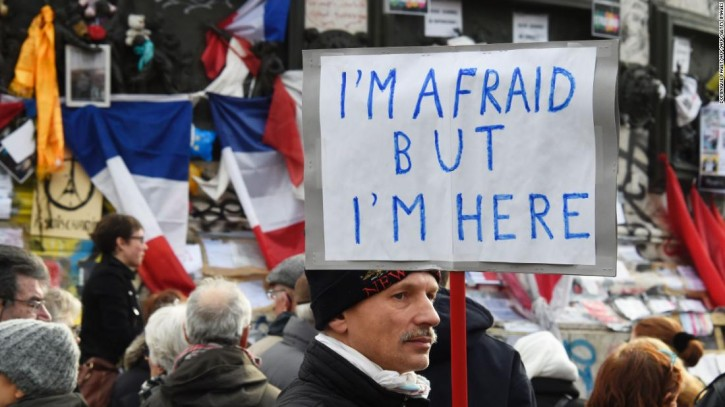 """FILE - A man holding a placard reading """"I am afraid but I am here"""" during a gathering on Place de la Republique (Republic square) on January 10, 2016 in Paris, as the city marks a year since 1.6 million people thronged the French capital in a show of unity after attacks on the Charlie Hebdo newspaper and a Jewish supermarket. EPA"""