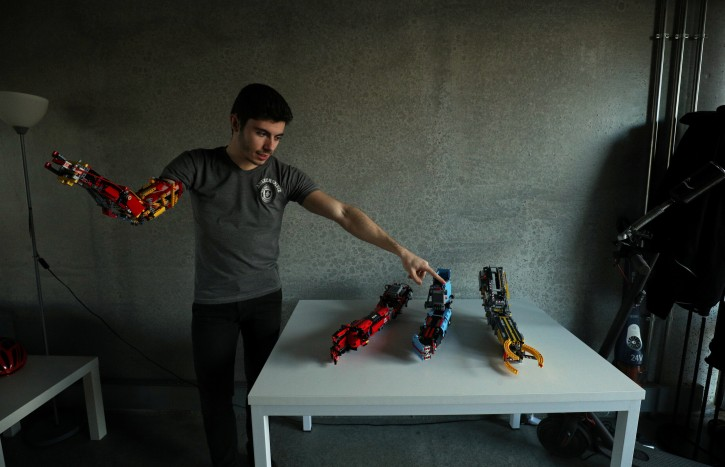 David Aguliar points at his prosthetic arms built with Lego pieces during an interview with Reuters in Sant Cugat del Valles, near Barcelona, Spain, February 4, 2019.REUTERS/Albert Gea