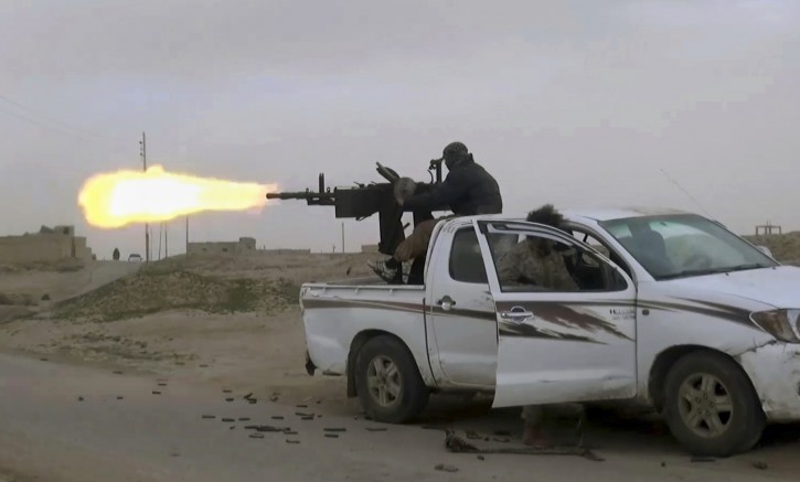 This frame grab from video posted online Friday, Jan. 18, 2019, by supporters of the Islamic State group, purports to show a gun-mounted IS vehicle firing at members of the U.S.-backed Syrian Democratic Forces (SDF) in the eastern Syrian province of Deir el-Zour, Syria.  (Militant Photo via AP)