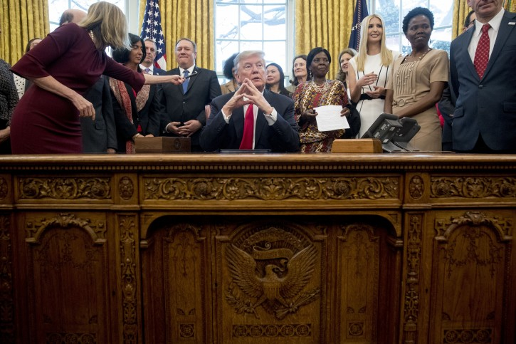 """President Donald Trump listens to a question from a reporter after signing the National Security Presidential Memorandum to Launch the """"Women's Global Development and Prosperity"""" Initiative in the Oval Office of the White House in Washington, Thursday, Feb. 7, 2019. Also pictured is Secretary of State Mike Pompeo, center left, and Ivanka Trump, the daughter of President Donald Trump, third from right. (AP Photo/Andrew Harnik)"""