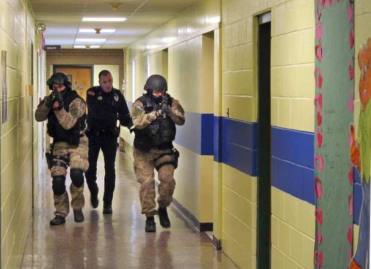 FILE - In this Jan. 28, 2013, file photo, members of the Washington County Sheriff's Office and the Hudson Falls Police Department use unloaded guns to take part in an emergency drill as they walk through a corridor inside the Hudson Falls Primary School in Hudson Falls, N.Y. AP