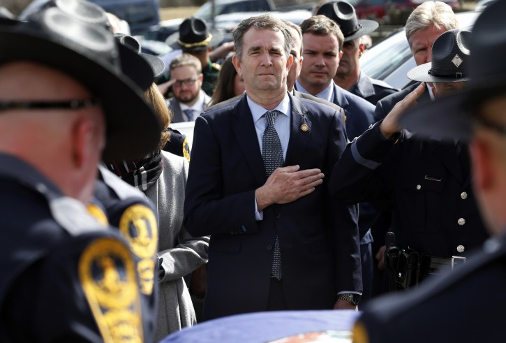 Virginia Gov. Ralph Northam, left,  and his wife Pam, watch as the casket of fallen Virginia State Trooper Lucas B. Dowell is carried to a waiting tactical vehicle during the funeral at the Chilhowie Christian Church in Chilhowie, Va., Saturday, Feb. 9, 2019. Dowell was killed  in the line of duty earlier in the week. (AP Photo/POOL/Steve Helber)