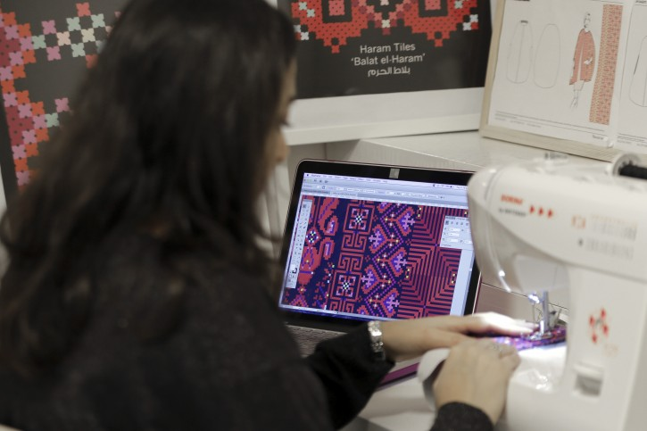 """In this Tuesday, Jan. 29, 2019 photo, designer Natalie Tahhan works in her studio in east Jerusalem. The thobe, a brightly embroidered robe for women, has long been a staple of Palestinian life, sewn by village women and worn at weddings and parties.  Tahhan produces capes from digital prints that replicate traditional embroidery stitches, """"connecting tradition with what is new and stylish."""" (AP Photo/Mahmoud Illean)"""