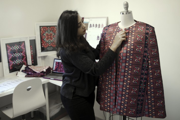 """In this Tuesday, Jan. 29, 2019 photo, designer Natalie Tahhan works on a modern version of the traditional Palestinian thobe in her studio in east Jerusalem. Tahhan, a designer based in east Jerusalem, produces capes from digital prints that replicate traditional embroidery stitches, """"connecting tradition with what is new and stylish."""" The thobe has long been a staple of Palestinian life, sewn by village women and worn at weddings and parties. (AP Photo/Mahmoud Illean)"""
