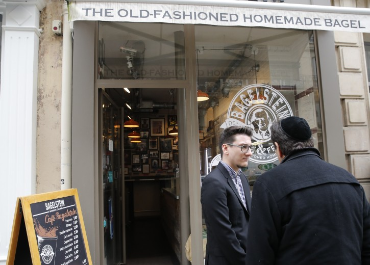 """Bagel shop owner Alexandre Jankowiak, center, which shop was sprayed with the German word """"Juden"""" on its front window last week, talks with a member of the Jewish community in Paris, Tuesday, Feb.12, 2019. According to French authorities, the total of registered anti-Semitic acts rose to 541 in 2018 from 311 in 2017, a rise of 74 percent. (AP Photo/Christophe Ena)"""