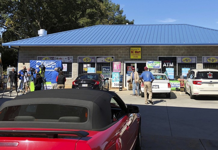 Media at left, record people entering the KC Mart in Simpsonville, S.C., on Wednesday, Oct. 24, 2018, after it was announced the winning Mega Millions lottery ticket was purchased at the store. Unless the winner chooses to come forward, the world may never know who won. (AP Photo/Jeffrey Collins)