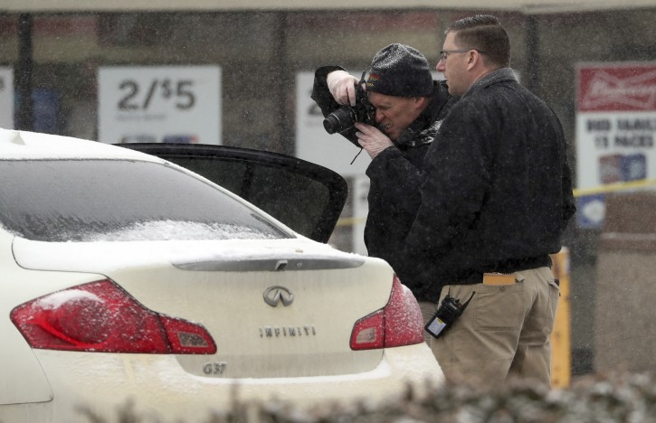 Investigators make photos of a vehicle outside a convenience store in Garnerville, N.Y., Wednesday, Feb. 20, 2019, after the vehicle reportedly struck and injured several people, five of them children. Police say the driver of the vehicle has been taken into custody for questioning. (Peter Carr/The journal News via AP)