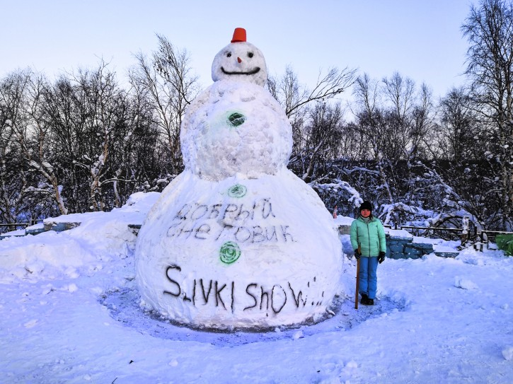 In this handout photo taken on Friday, Feb. 8, 2019 and released by Anna Zorina, a woman stands with a meter measuring ruler next to a snowman in the Arctic Circle city of Severomorsk, Russia. Building a snowman isn't always just a way to while away a long winter. For some in Russia and Ukraine, it's a way to possibly earn some significant money. (Anna Zorina via AP)