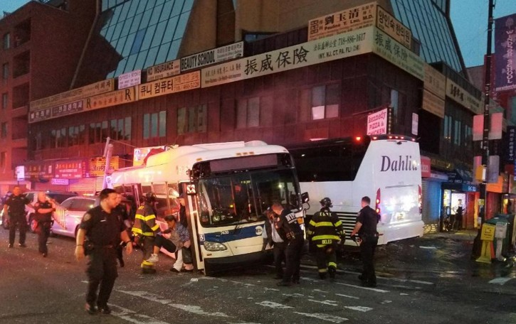 In this photo provided by the NYPD's 109th  Precinct, is a collision involving two buses on Main St. in the Queens borough of New York, Monday, Sept. 18, 2017. The Fire Department of New York says 17 people have been hurt, seven of them severely, when a city bus and a tour bus collided in the Flushing neighborhood. (NYPD's 109th Precinct via AP)