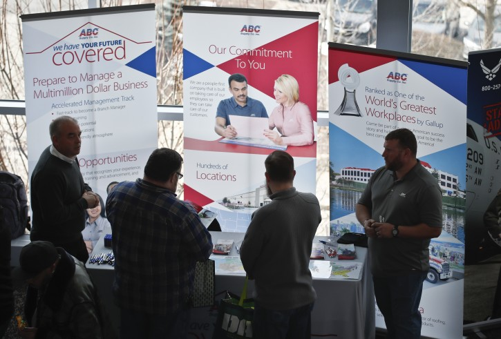In this photo made on Thursday, March 7, 2019, visitors to the Pittsburgh veterans job fair meet with recruiters at Heinz Field in Pittsburgh. (AP Photo/Keith Srakocic)