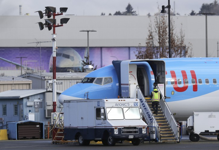 A worker walks up steps to the right of an avionics truck parked next to a Boeing 737 MAX 8 airplane being built for TUI Group at Boeing Co.'s Renton Assembly Plant Wednesday, March 13, 2019, in Renton, Wash. (AP Photo/Ted S. Warren)