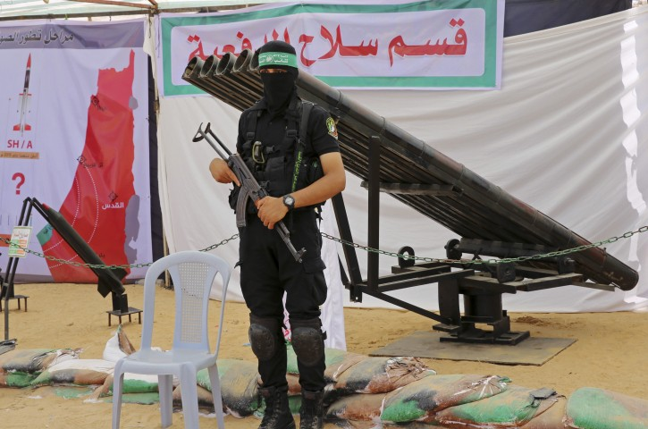 A Palestinian militant from the Izzedine al-Qassam Brigades, a military wing of Hamas, stands in front of rockets launcher during a weapon exhibition at Hamas youths summer camp in Gaza City, Wednesday, July 20, 2016. (AP Photo/Adel Hana)