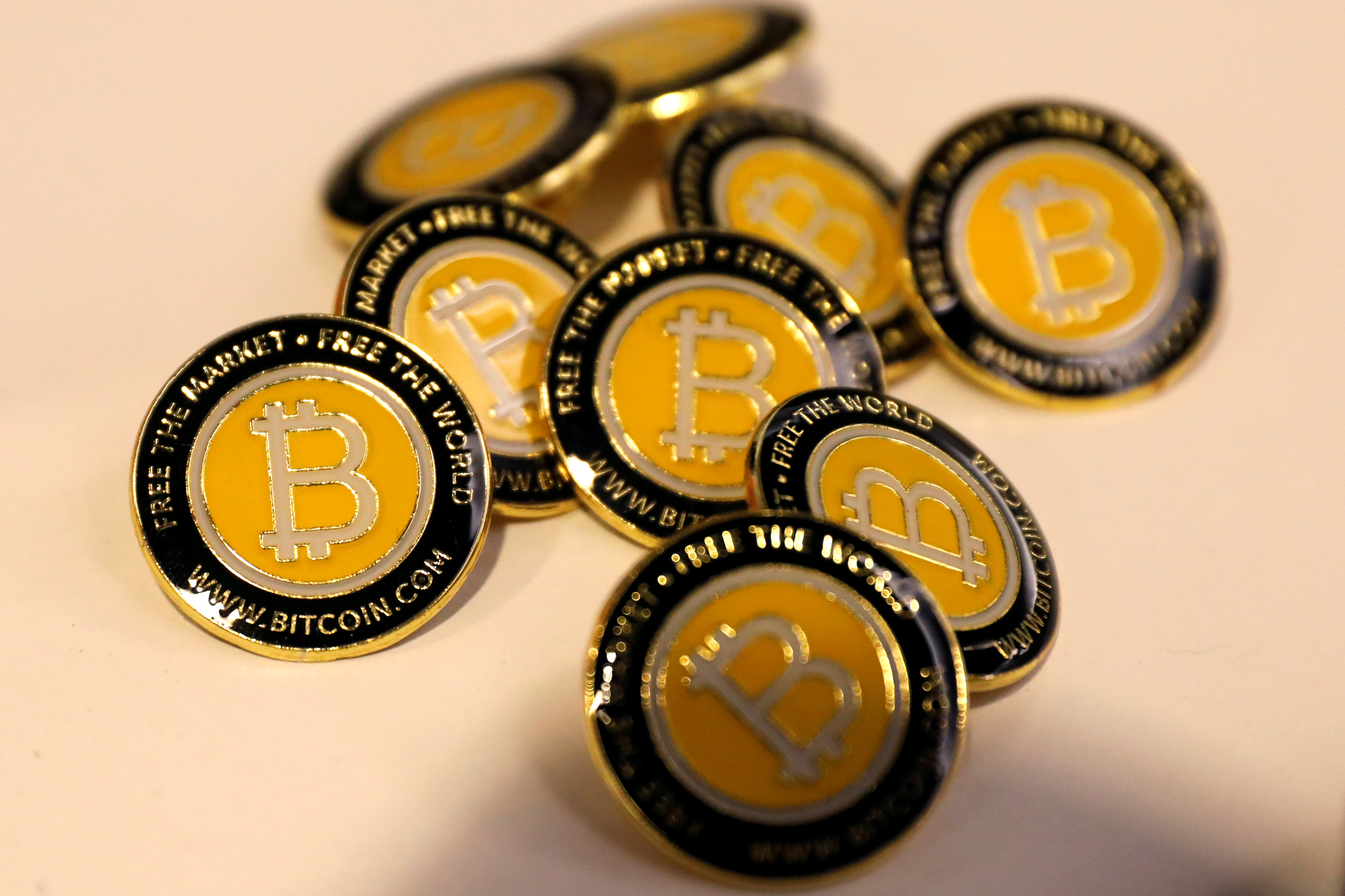 FILE - Bitcoin.com buttons are seen displayed on the floor of the Consensus 2018 blockchain technology conference in New York City, New York, U.S., May 16, 2018. REUTERS/Mike Segar/File Photo