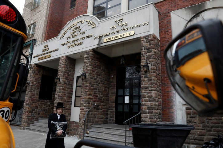 FILE - An Orthodox Jewish man walks by the Yeshiva Kehilath Yakov school on the day New York City Mayor Bill de Blasio declared a public health emergency in parts of Brooklyn in response to a measles outbreak in New York City, U.S., April 9, 2019. REUTERS/Shannon Stapleton