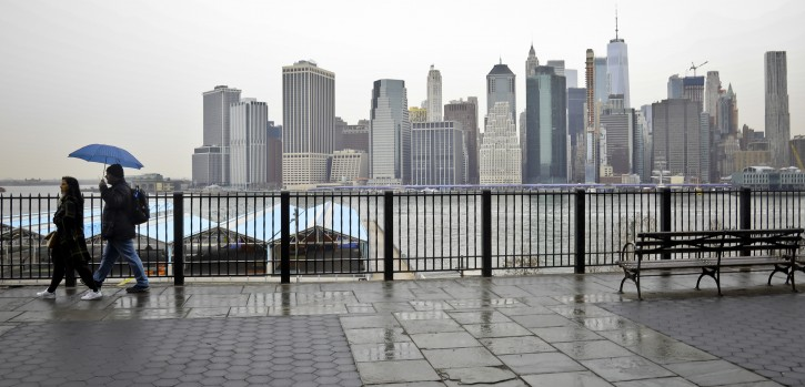 Visitors walk along Brooklyn Heights Promenade during a rainy day Friday April 5, 2019, in New York.  The promenade makes up the top deck over-hang of a deteriorating Brooklyn-Queens Expressway and the city's plans for repairs has drawn neighborhood protest, since it calls for a temporary six lane highway on the promenade.  (AP Photo/Bebeto Matthews)