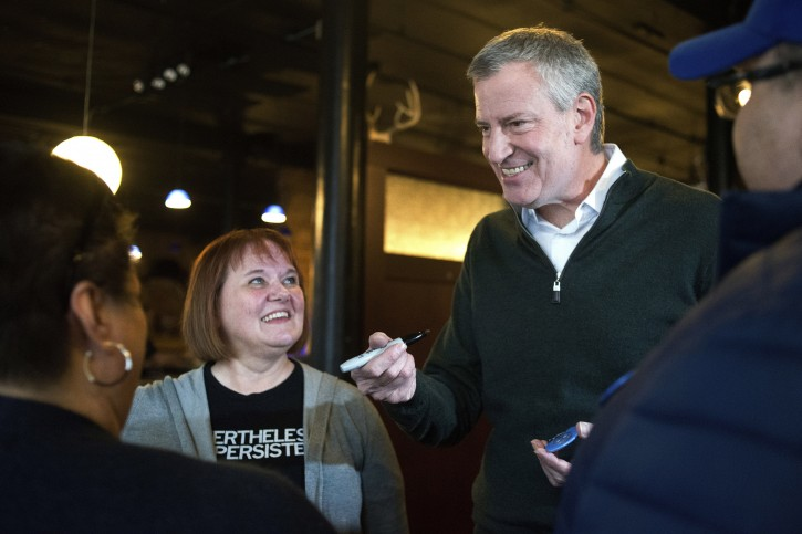 FILE - This Feb, 23, 2019 file photo shows New York City Mayor Bill de Blasio as he gives his autograph to Sandi O'Brien, left, of Sioux City, left, before an event hosted by the local Democratic party in Sioux City, Iowa. AP