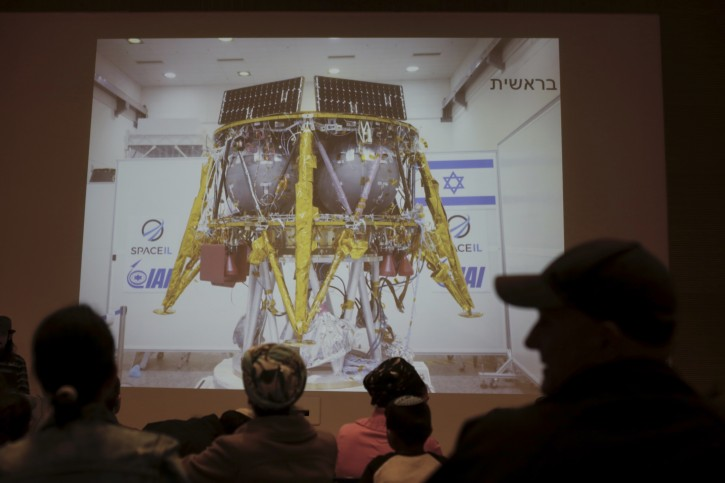 People watch the live broadcast of the SpaceIL spacecraft as it lost contact with Earth in Netanya, Israel, Thursday, April 11, 2019. (AP Photo/Ariel Schalit)