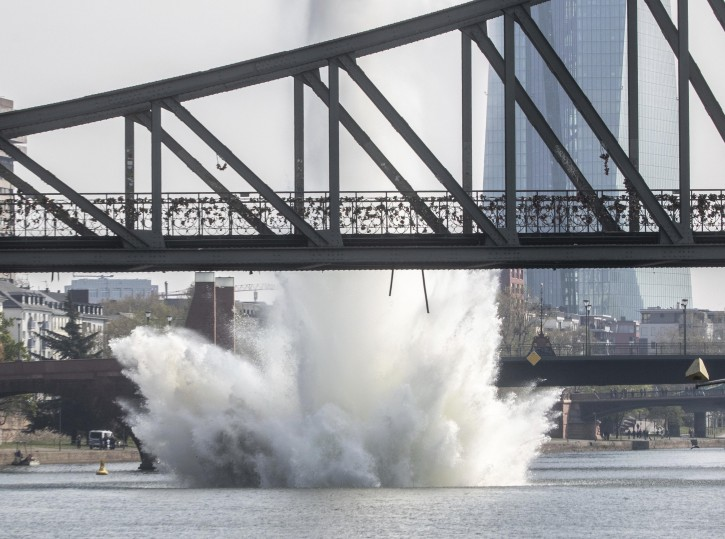 A large water fountain rises behind the Iron Bridge when a 250 kilogram US-American bomb from the Second World War in the Main River is detonated with a blast in Frankfurt, Germany, Sunday, April 14, 2019. About 600 people had to leave their homes for security reasons. On the right in the background you can see the headquarters of the European Central Bank (ECB). (Frank Rumpenhorst/dpa via AP)