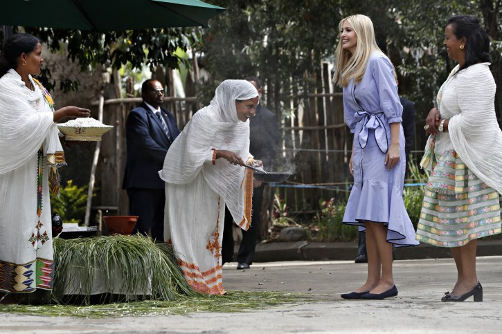 A woman bows while roasting coffee beans as another holds out a bowl of popcorn as they greet White House senior adviser Ivanka Trump, with Moya founder Sara Abera, as she arrives at the manufacturing center of textile and traditional crafts, Sunday April 14, 2019, in Addis Ababa, Ethiopia. AP