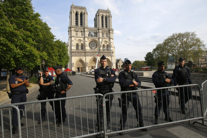 Police officer stand behind the security barriers in front of Notre Dame cathedral Thursday, April 18, 2019 in Paris.