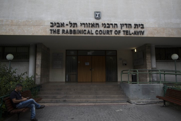 FILE - A man sits outside the Rabbinical Court in Tel Aviv on November 27, 2013. Photo by Yonatan Sindel/Flash90
