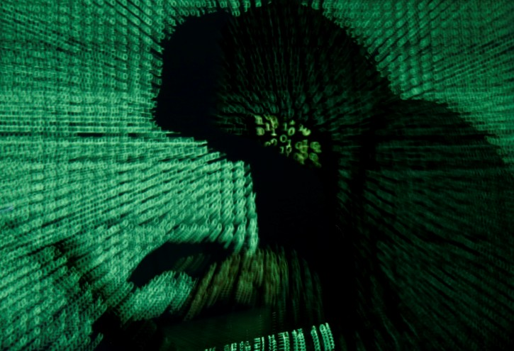 FILE - A man holds a laptop computer as cyber code is projected on him in this illustration picture taken on May 13, 2017. REUTERS/Kacper Pempel/Illustration