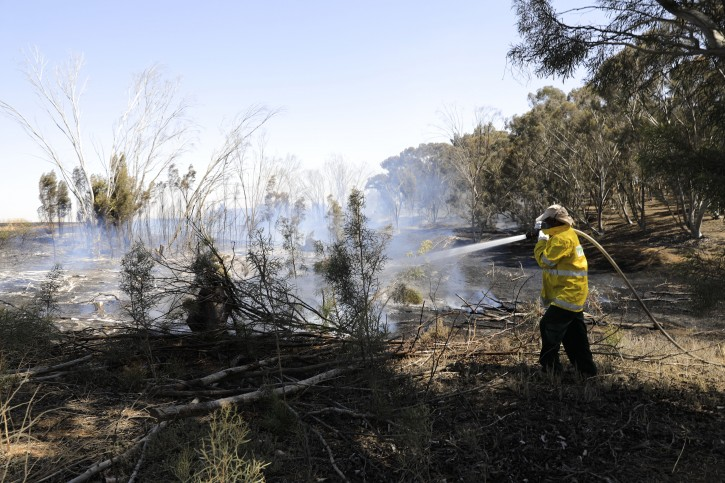 Israeli firefighter battles a fire started by an incendiary device launched from Gaza Strip, near the Israel and Gaza border fence, Wednesday, May 15, 2019.(AP Photo/Tsafrir Abayov)