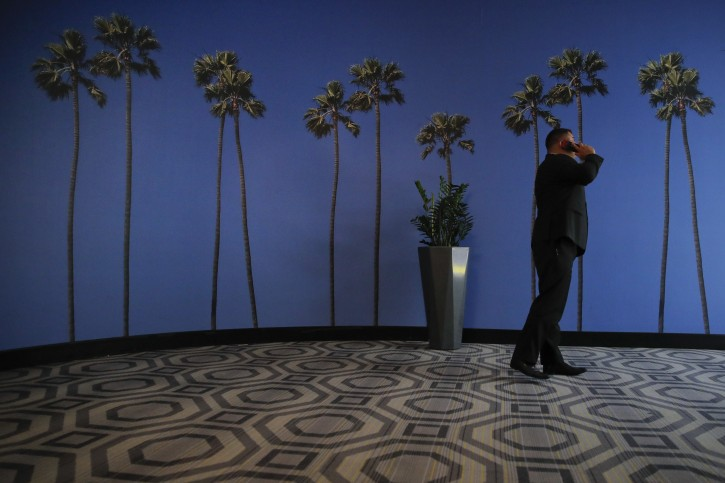 FILE - In this May 4, 2018, file photo a man talks on the phone in a hallway adorned with the palm tree-printed wallpaper at a hotel near the Los Angeles International Airport in Los Angeles. (AP Photo/Jae C. Hong, File)