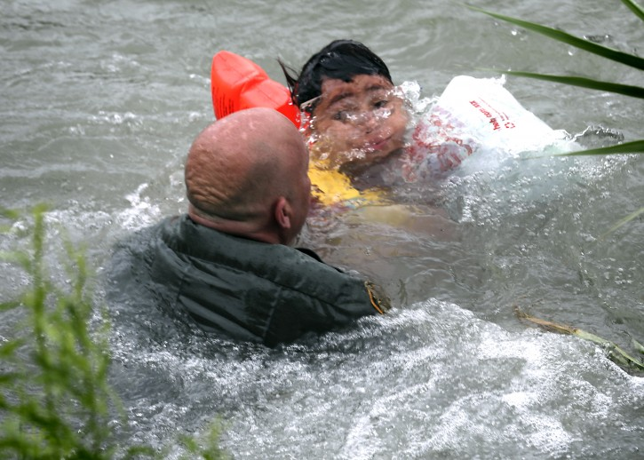 Border Patrol Agent Brady Waikel rescues a seven year old boy from Honduras after he fell out of a make shift raft and lost hold of his mother as Border Patrol agents respond to three rafts crossing the Rio Grande River in Eagle Pass, on Friday, May 10, 2019.