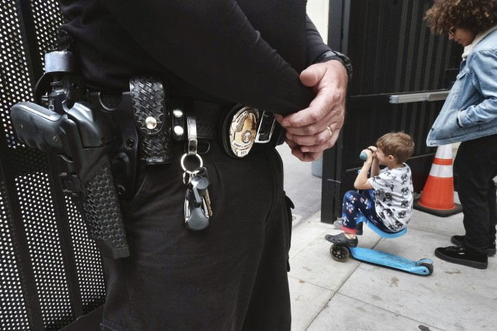 In this Monday May 13, 2019 photo a security guard stands in watch at Beverly Hills Unified School District's K-8 Horace Mann School as students prepare to leave school for the day in Beverly Hills, Calif. (AP Photo/Richard Vogel)