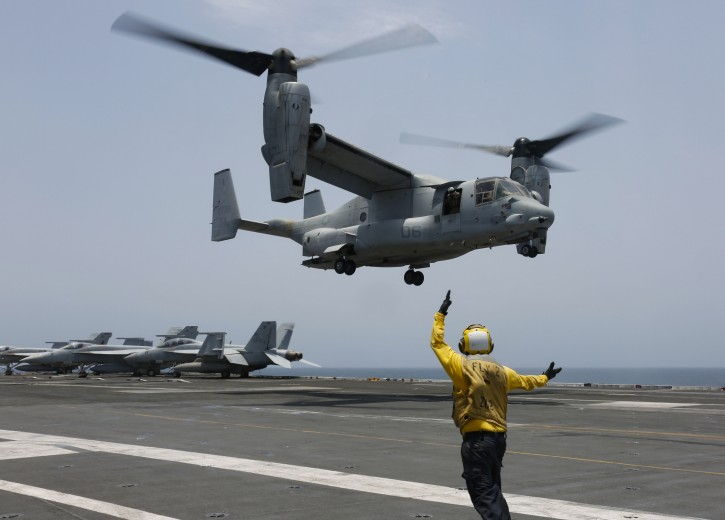 """In this Friday, May 17, 2019, photo released by the U.S. Navy, Aviation Boatswain's Mate 2nd Class Nicholas Hawkins, from Houston, Texas, signals an MV-22 Osprey to land on the flight deck of the Nimitz-class aircraft carrier USS Abraham Lincoln in the Arabian Sea. Commercial airliners flying over the Persian Gulf risk being targeted by """"miscalculation or misidentification"""" from the Iranian military amid heightened tensions between the Islamic Republic and the U.S., American diplomats warned Saturday, May 18, 2019, even as both Washington and Tehran say they don't seek war. (Mass Communication Specialist 3rd Class Amber Smalley/U.S. Navy via AP)"""