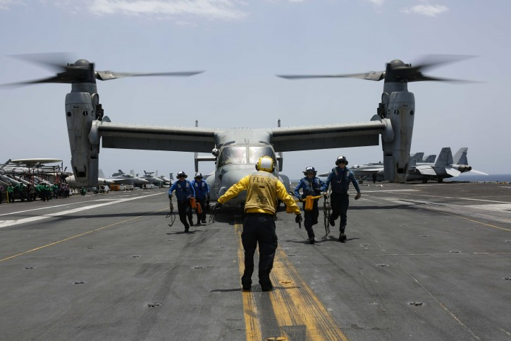In this Friday, May 17, 2019, photo released by the U.S. Navy, sailors work around an MV-22 Osprey as it lands on the flight deck of the Nimitz-class aircraft carrier USS Abraham Lincoln in the Arabian Sea. AP